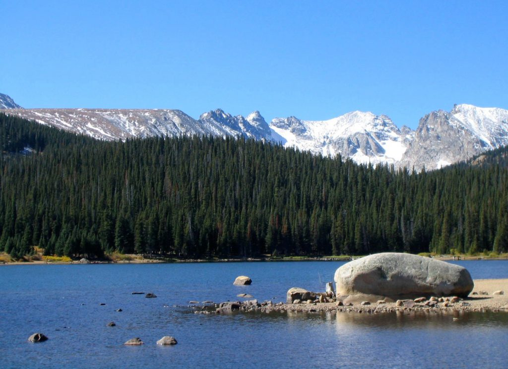 View of the snowcapped Continental Divide in Colorado with lake and huge rock in foreground