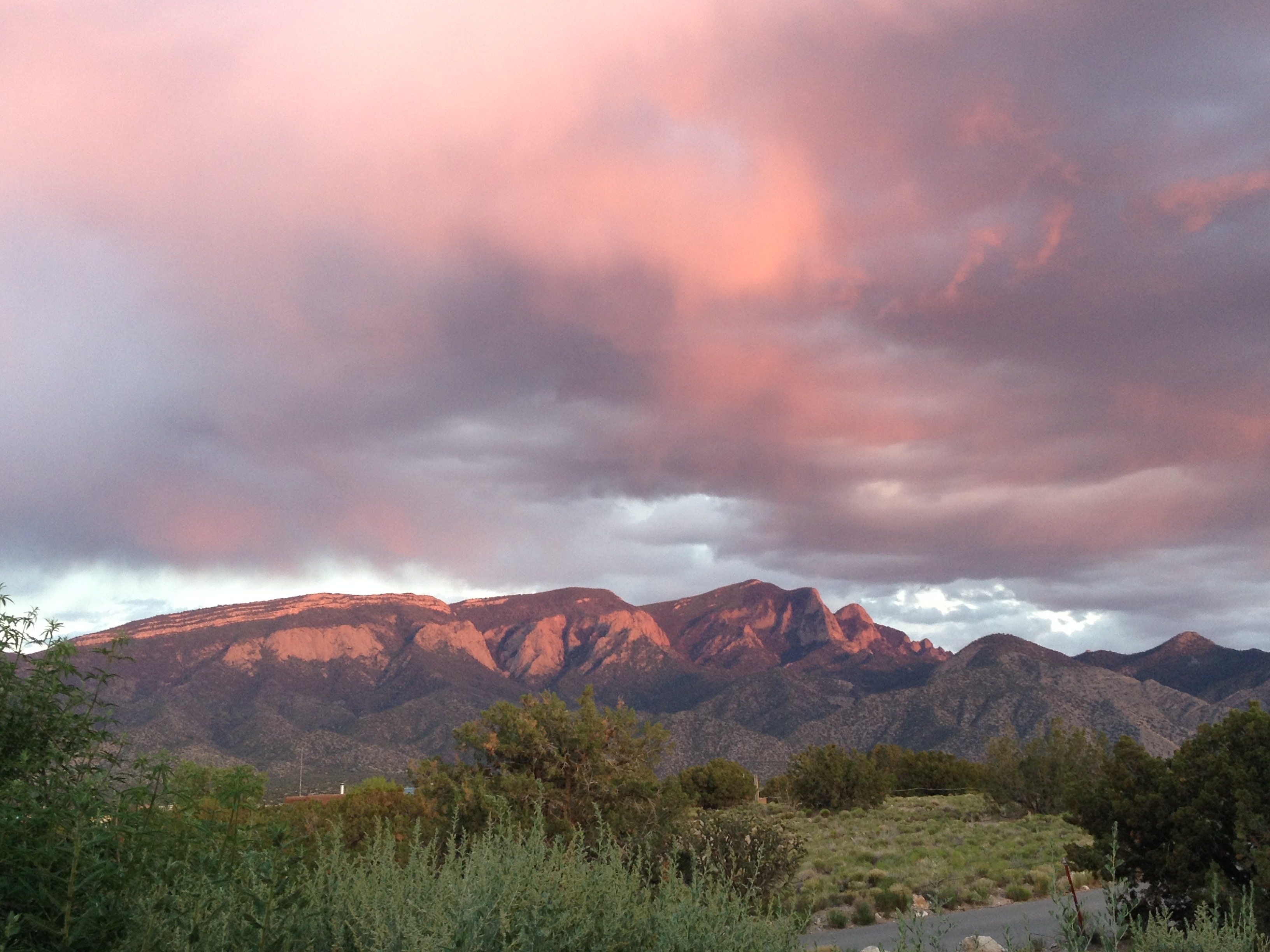 View of Sandia Mountains on a cloudy sunset, mountain face and clouds lit up bright pink.