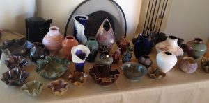 Dozens of ceramic pots of different shapes and colors and styles laid out on a table in front of a kiva fireplace