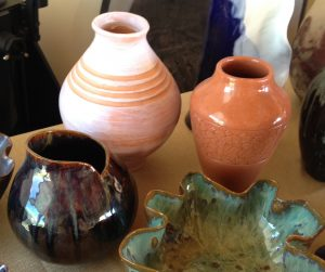 Tall terra-cotta vases, a round brown-black shiny pot, a green-glazed bowl with scalloped edges