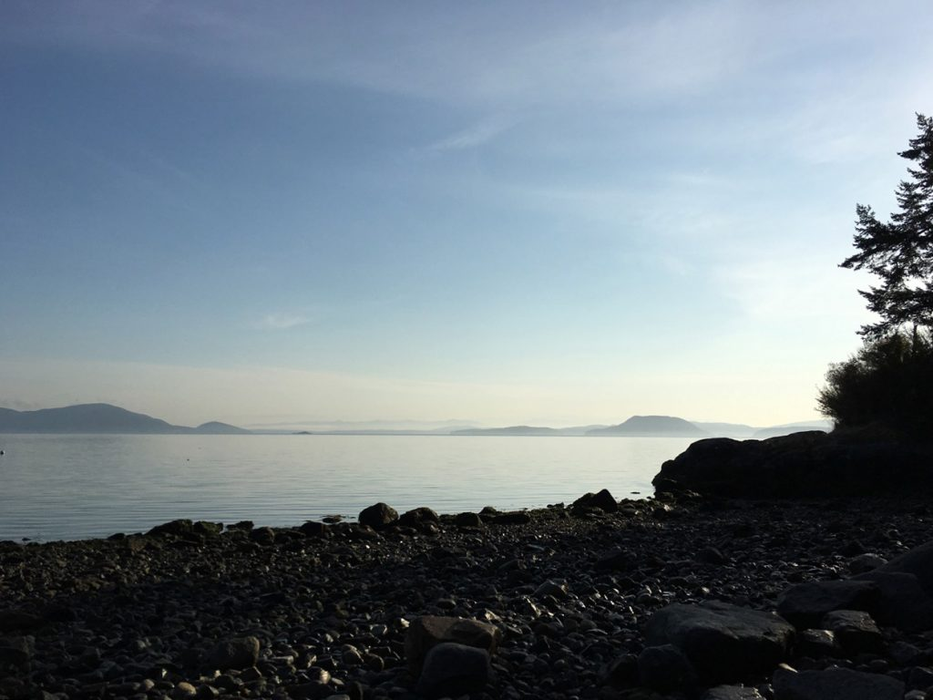 Clear sky, silhouette of rockey shore with light at horizon