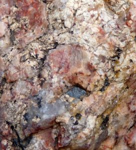 Close-up of rock surface with reddish and white crystalline segments