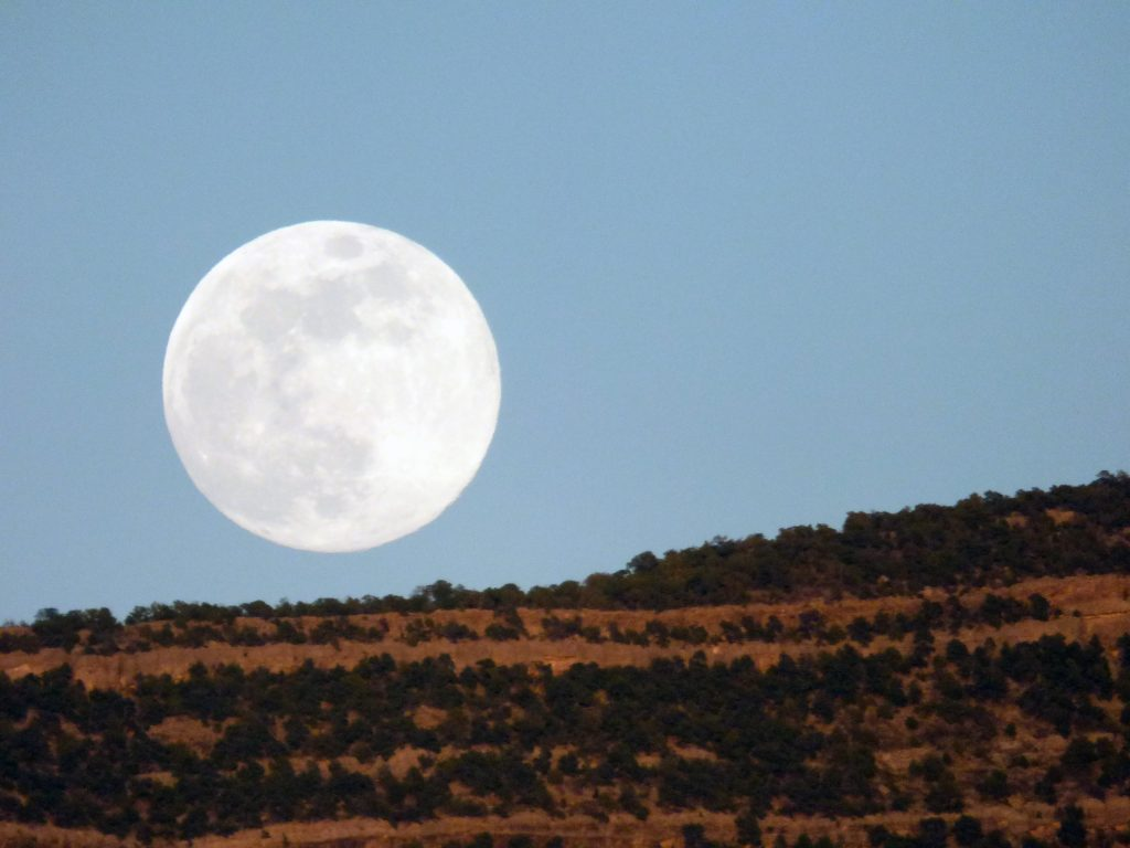 An enormous full moon just clearing a red rock cliff against a twilight sky.