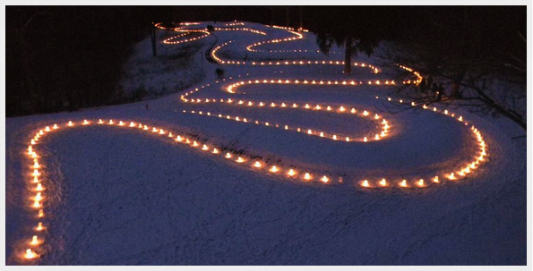 Nighttime photo of candles outlining a snow-crusted Serpent Mound