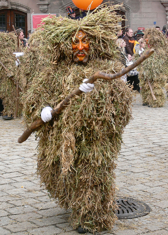 Human in fuzzy straw costume with mask parading down a street