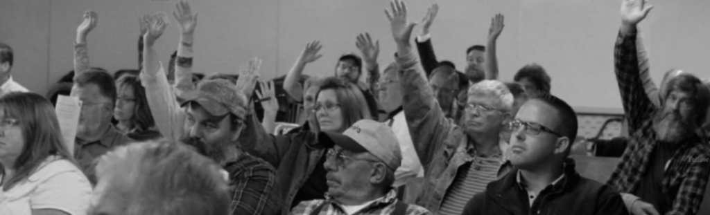 Regular folk in a public meeting raising their hands to vote for a community rights ordinance