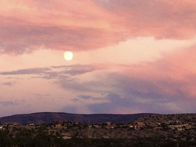 Moon rises among pink and lavender clouds over desert landscape. Opening to beauty is one part of opening to truth.