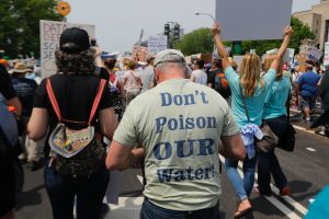 Back of a group of protesters. The man in front of the camera wears a T-shirt reading Don't Poison Our Water.